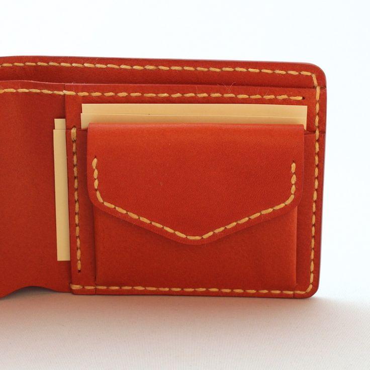 ハンドメイドの小銭入れ付き二つ折り財布。ナチュラルな質感の革は味わい深く育ちます。大きく開く小銭入れが付き。シンプルなデザインなのでメンズ・レディース問いません。名入れや糸色のカスタマイズもお受けしています。