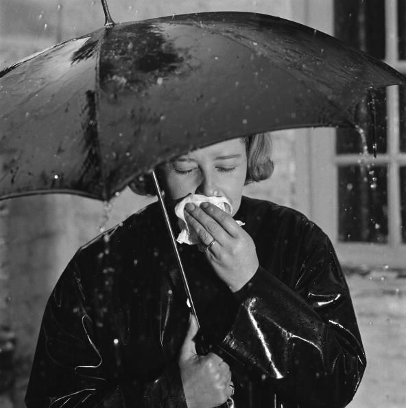 A woman out walking in the rain with a bad cold, 26th August 1965. The shot was taken to advertise Beechams cold and flu medicines.