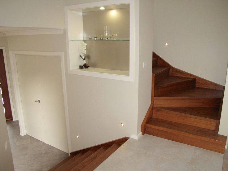 Contemporary entrance including  metallic recessed display case with glass shelves