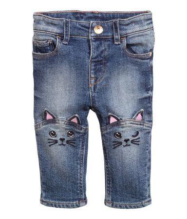 Vaqueros de cinco bolsillos en algodón elástico y lavado con cintura elástica ajustable, cierre con botón de presión, y bordados y aplicaciones decorativas en las rodillas.