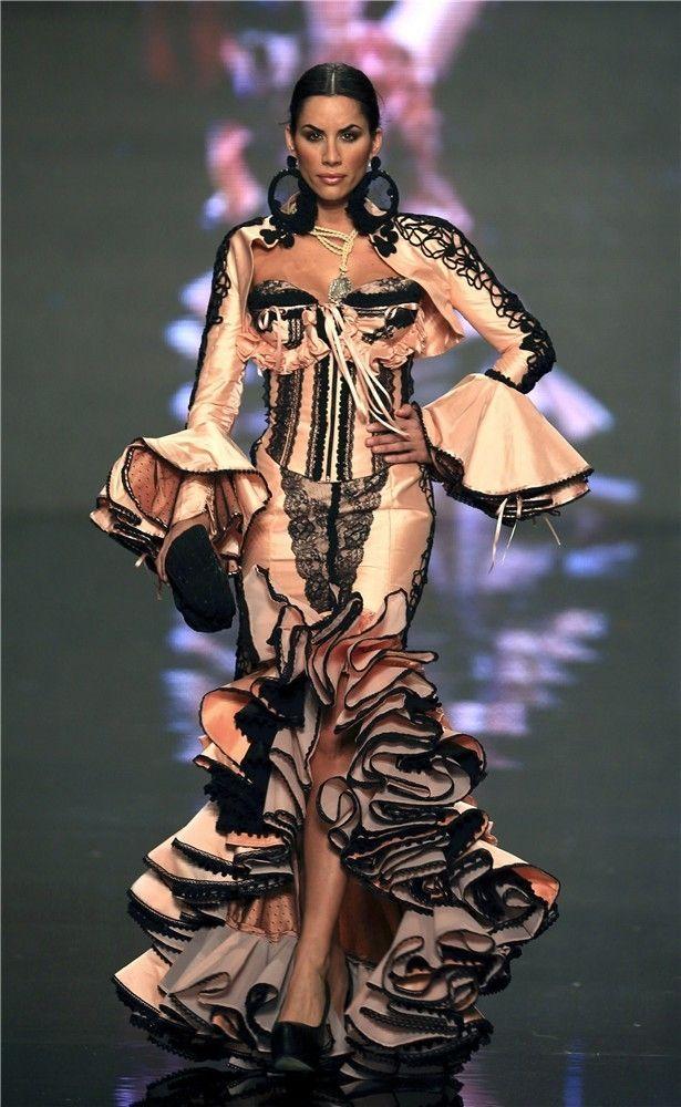 Inspirado en las corridas goyescas, vestido de flamenca ajustado realizado en satén, volantes y encajes en negro sobre fondo nude. La falda asimétrica permite ver las piernas de la modelo.