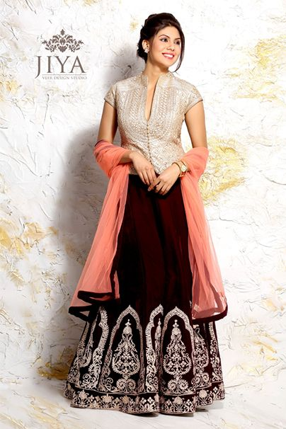 A contemporary lehenga styled like a skirt and corset. A pearl jacket like choli completely hand embroidered with resham, styled with a smart neckline and cutout back. The wine colored lehenga or kali skirt is also embroidered with the resham embroidery in chandelier style. The style comes with a coral net dupatta.