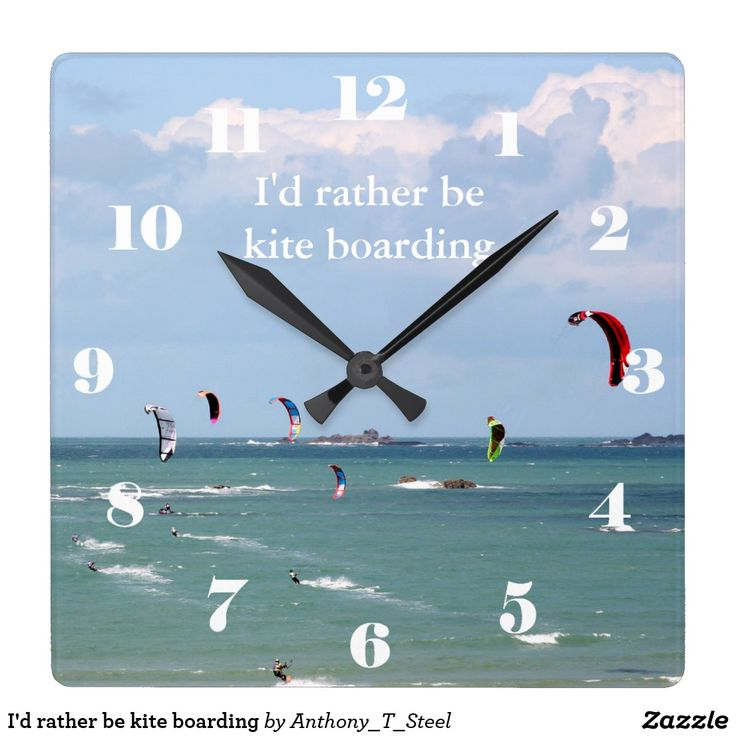 """I'd rather be kite boarding square wall clock A square clock covered by a photo of a kite boarding race in progress off the coast of St Malo, Brittany, France, with white numbers makes a great gift for anyone who loves to kite board. It has the text """"I'd rather be kite boarding"""" on its face."""