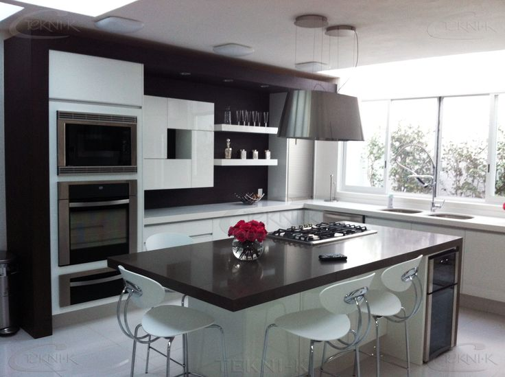 El diseño de esta cocina está centrado en una isla con parrilla y mesa desayunador o de trabajo; en Cuarzo Oscuro con un remate del mismo en forma de grapa. Los gabinetes y alacenas lo hacen resaltar, por el color blanco liso del que están construidos.