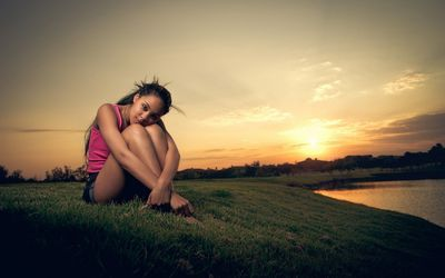 Cute brunette in the grass at sunset wallpaper