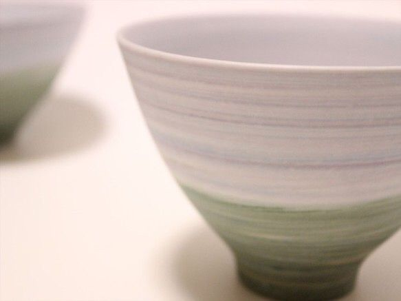 「彩磁」色の異なる磁器土や釉薬を混ぜ合わせて作り練り上げという技法で、独特な色彩、質感を作っています。ブルーとグリーンの2トーンの茶碗です。おかずを盛り付ける小鉢として、深めに形作っているため汁物にもご使用いただけます。私は花弁を水に浮かべて花入としても使用しています。普段使いの器にしていただければ幸いです。Size口縁直径:約12.7cm高さ:約7.8cm重さ:250gSign:HARU制作:2014年商品画像はできるだけ実物に合わせておりますが、お客様のモニター環境によっても多少異なることがありますので、ご了承ください。 陶芸家 中川智治自分が美しいと感じる「形」、「色彩」、「気配」をテーマにうつわを制作しています。何年、何十年と使い続けてもらえるような「うつわ」を目指して日々制作しています。HP:http://potter-ash-field.com****************略歴******************** ■2015年11月 西荻窪 東の風 個展   ■2015年9月 東急百貨店本店 個展 ■2015年7月 HandMade In Japan Fes…