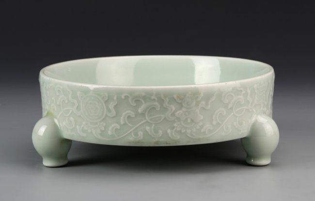 China, antique celadon glazed tripod brush washer, with three rounded feet, and white floral motif, with Yongzheng mark. Height 3 in., Diameter 7 3/4 in.