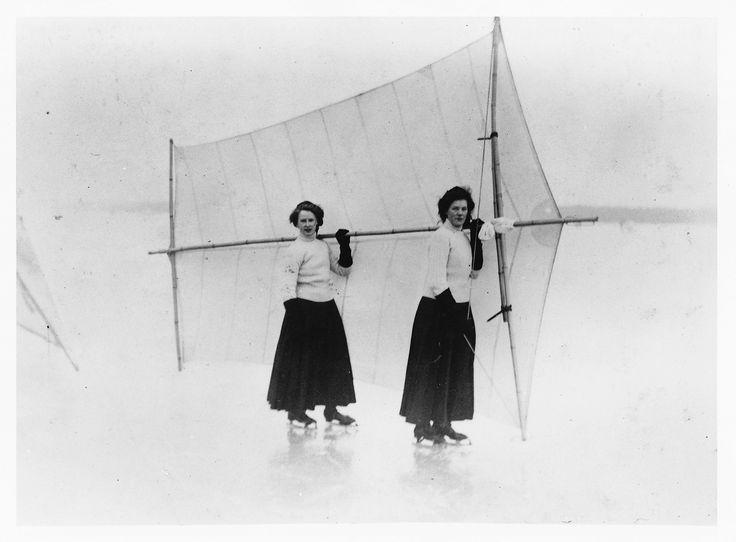 Skridskosegling på is. Två kvinnor i tidens sportkläder, långa kjolar och polotröjor, och på skridskor håller gemensamt upp ett skridskosegel bakom sig. Fotograf: Okänd, ca 1905-1915