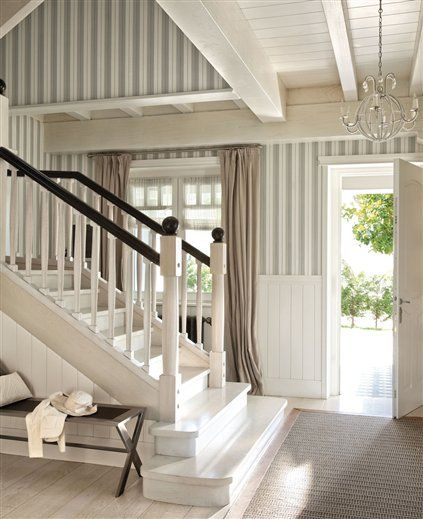 country classic entry.  white architecture, bleach wood floors, and striped walls.