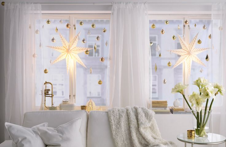 Ein weißes Sofa, das vor einem Fenster mit weißer und goldfarbener Weihnachtsdeko hängt, u. a. STRÅLA Hängedekorationen Stern/glänzend weiß.