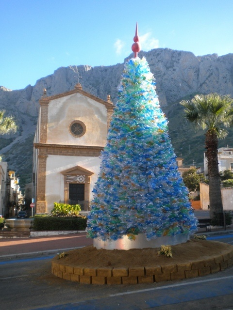 The main square of Cinisi, in the province of Palermo, proudly displays its eco-friendly Christmas tree. The tree was created by a team of enthusiastic youngsters led by Vincenzo Cusumano, the creator and art director. 6,000 plastic bottles were used to build this 23 ft. tree. The effect is spectacular, especially in the evening, when the lights create a special effect.