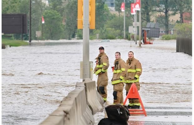 Calgary firefighters stand on a flooded Macleod Trail on Friday morning June 21, 2013.  Photograph by: Gavin Young, Calgary Herald      Read more: http://www.calgaryherald.com/Live+gallery+Latest+pictures+from+flood+ravaged+Alberta/8559569/story.html#ixzz2Wsp2S9nC