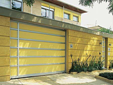 Os frisos do portão dão continuidade ao desenho do muro de alvenaria, coberto com textura Terracor. Sobre o alumínio, aplicou-se um fundo de galvite (um tratamento de galvanização) antes da tinta acrílica acetinada amarela. Projeto de Mari Ani Oglouyan.