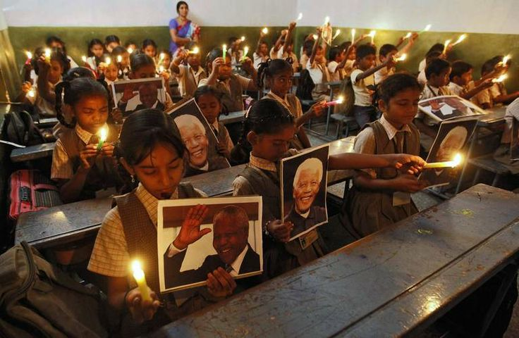 Schoolchildren hold candles and portraits of former South African President Nelson Mandela during a prayer ceremony at a school in the weste...