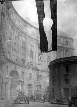 "Flag of Hungary, 1956, with the communist coat of arms cut out. The flag with a hole became the symbol of the revolution. (Photographed at the ""Corvin köz"")  Source: Wikpedia"