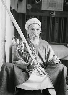 """A Yemenite Jew named Yehia holding the 4 species in the sukka (1939) Yehia, the Yemenite Jew pictured here, was almost certainly part of a large migration of Jews who arrived in Jerusalem in the 1880s, well before the famous """"Magic Carpet"""" operation that brought tens of thousands to the new state of Israel during 1949 and 1950."""