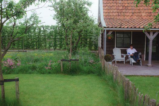Landelijke boerderijtuin met veranda, fruitbomen en lang bloemrijk gras.