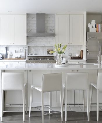 Sensational white kitchen design with white Ikea kitchen Cabinets, HanStone Quartz Countertops, sink in marble kitchen island, instant heat faucet, HomeSense white modern leather counter stools, marble subway tiles backsplash, gray, travertine, tiles, floor