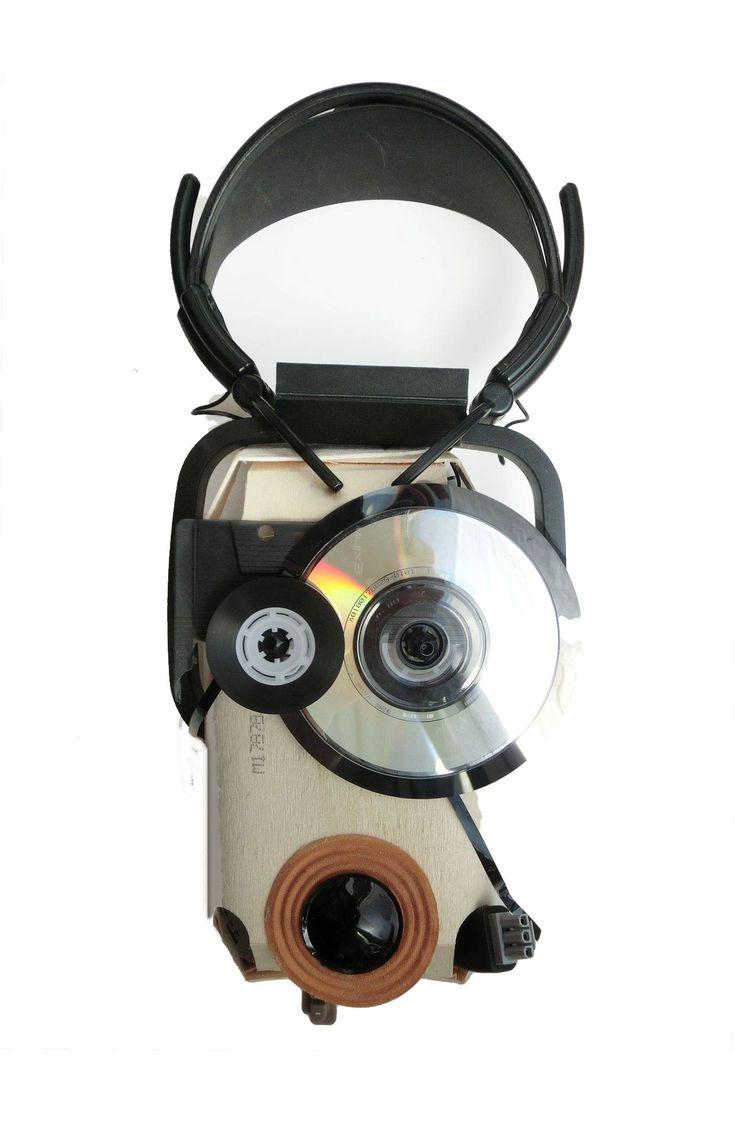 » der Whistle-Blower «  Bricolage 2013, 18 x 35 x 7cm   Material: Kassetenband aufgerollt auf Spule, halbe Kassette, Innereien eines Lautsprechers, CD mit CD-Halterung, 3-Pol Stecker, Gummitasten, Kopfhörer  Medium: Sperrholz Verpackung eines Biobrotes
