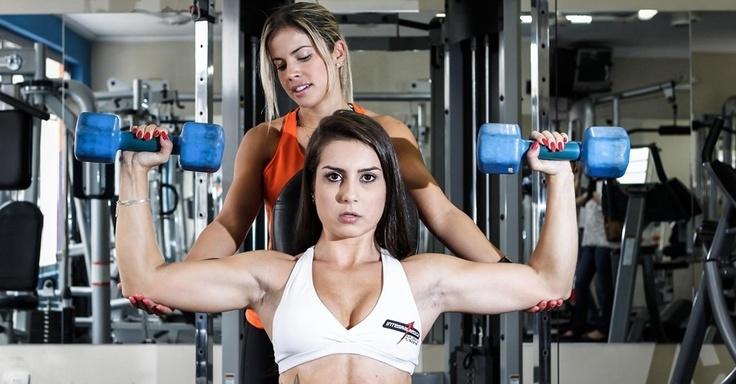 Para trabalhar os músculos das costas e tríceps, Nathália faz o desenvolvimento com halteres. Sente-se em um banco com as costas retas e os halteres ao nível dos ombros