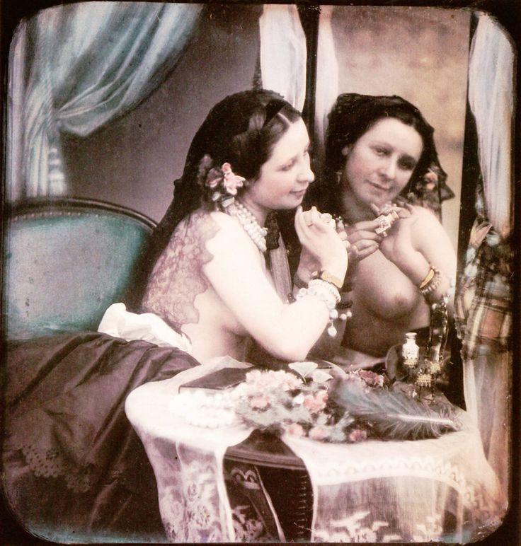Mujer semidesnuda, con el pecho al descubierto y con un collar de perlas, se mira en el espejo.  Daguerrotipo estereoscópico coloreado a mano. 1850.