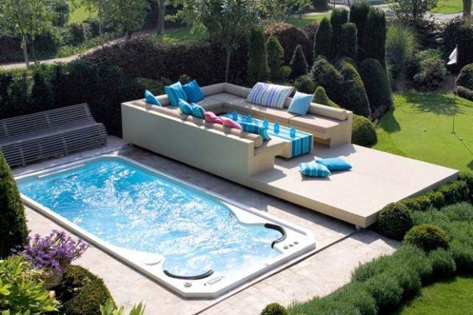 Spa de nage Acylique modèle Aquasport extérieur avec terrasse surélevée et salon de jardin contemporain© Clair Azur Spas