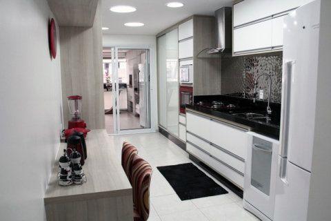 O mobiliário branco serve de pano de fundo para o tampo preto da bancada e para o revestimento cromado da parede. Na torre de fornos, só uma parte ganhou detalhes em vermelho. Projeto de Adriana Braggion.