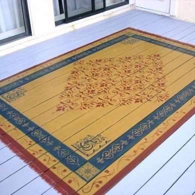 Painted Exterior Rug A rug can make an outdoor space feel more like a room. To prove the point, see how this gorgeous painted rug warms up a gray wooden deck with a stenciled pattern in red, gold, and blue. If you are a DIY type, visit your local building supply or hardware store to find a stencil pattern you like   Painted Rug
