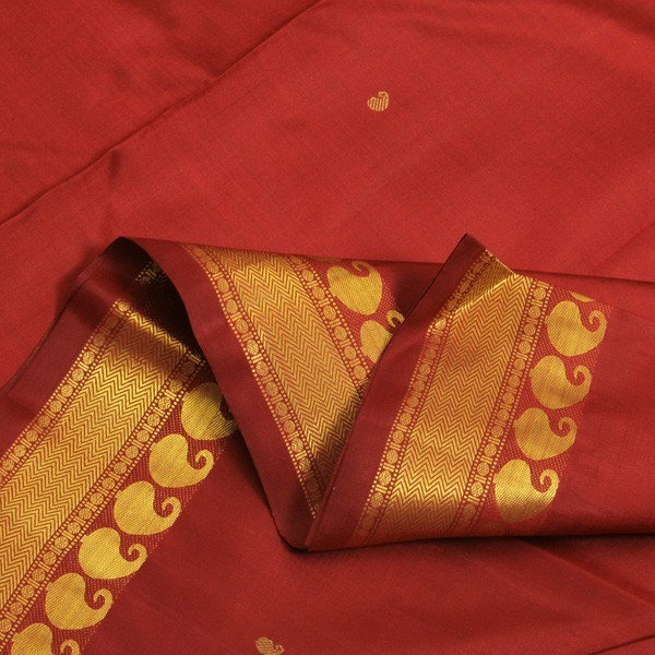 In this classic, regal Sarangi piece, the chosen emblem is the mango. On the body, the tiny dots of mangoes rain down, in sparse spacing, their golden luster very lovely against the sari's unapologetically deep maroon silks. The golden pallu echoes the mango motif, its graceful curves complemented by lines and slivers. Finally, the mango-lined border features rudraksham beads and zigzags, woven resplendently in gold.Code 070112219