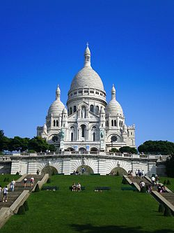 The Basilica of the Sacred Heart of Paris, commonly known as Sacré-Cœur Basilica (French: Basilique du Sacré-Cœur, pronounced [sakʁe kœʁ]), is a Roman Catholic church and minor basilica, dedicated to the Sacred Heart of Jesus, in Paris, France. A popular landmark, the basilica is located at the summit of the butte Montmartre, the highest point in the city.