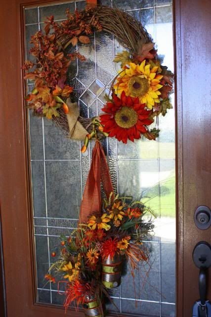 Darling door wreath.  I am loving the dangling upcycled cans filled with flowers!  Great idea!