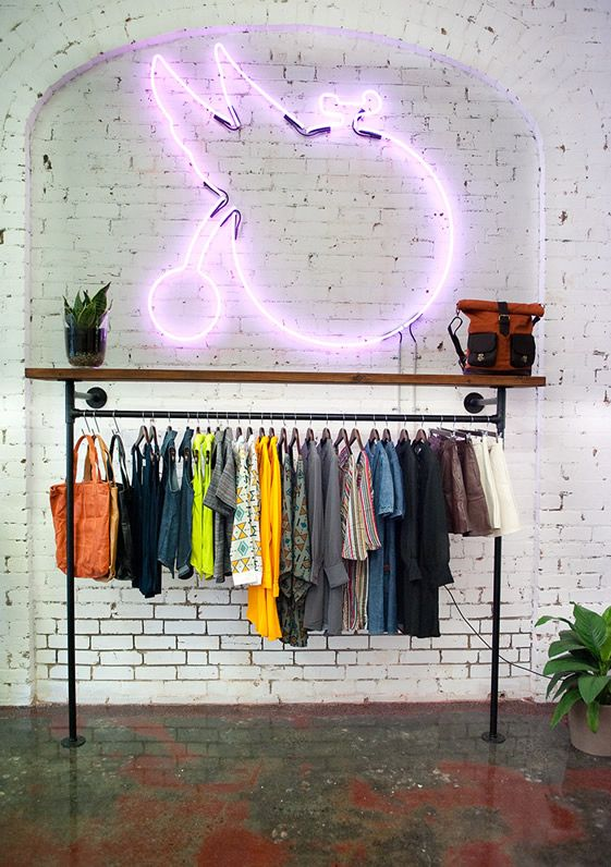 Industrial pipeline outriggers on wall for clothing rack.  Great use of space!