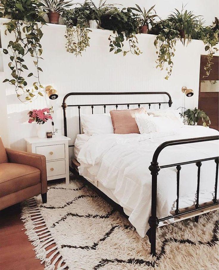 Schlafzimmer mit Eisenbett und vielen Pflanzen im urban jungle Look