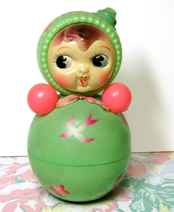 Sweet Vintage Green Celluloid Roly Poly Girl Doll Toy. It has a chiming bell inside and a whistle on the top that works when you blow into it! About