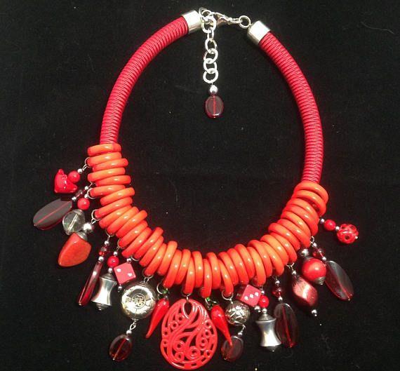 collier plastron rouge pièce unique. ce collier est un mélange de passementerie ,danneaux en verre de Murano,de perles en verre,en résine,en métal et en bois. fermoir mousqueton argent longueur du collier totale du collier 48 cm poids 207 gr