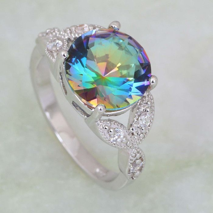 Adorned with a round-cut Mystic Fire Topaz center stone accentuated with cubic zirconia stones, this sterling silver ring exudes a luminous look. RING DETAILS - Width: 10 mm - Metal: sterling silver D