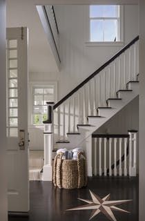Airy entry way with starburst floor inlay, white molding and dark wood accents   Hallway  Foyer  Staircase  Architectural Details  Shingle Style  Coastal by SLC Interiors