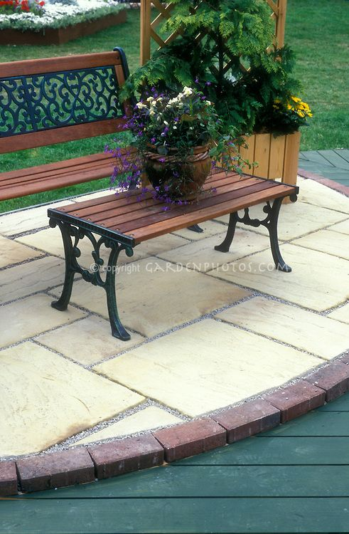 Stone paver patio edged in brick next to wood decking, with patio furniture and container of plants
