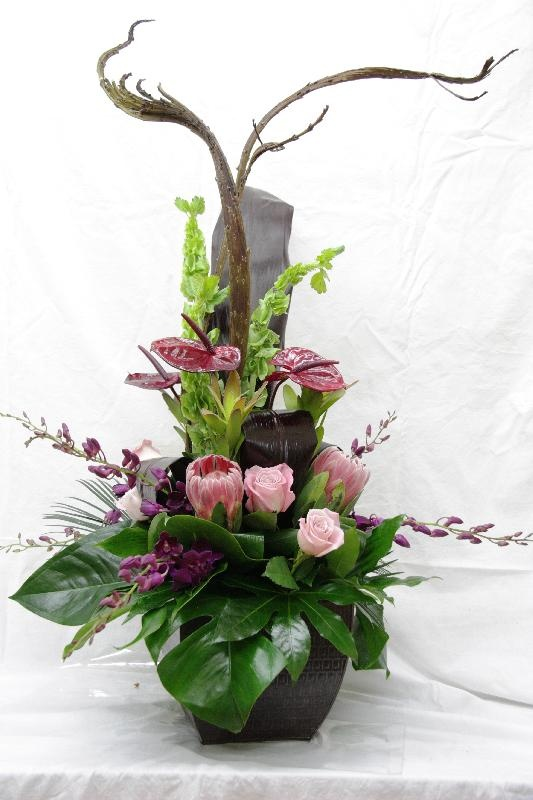Sympathy Flowers with bells of Ireland, anthurium, leucadendron, pink protea, roses, dendrobiums, red ti leaves, sago palm, natraj - take roses out and add another protea and leuc at base.