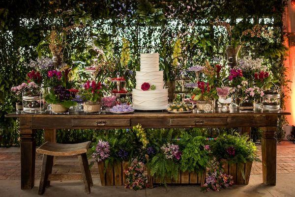 Mesa de doces em madeira rústica com flores lilás, rosa, pink e bolo de três andares branco. Foto: Rafael Bigarelli