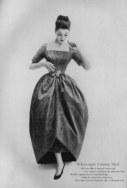 Renee Breton, November Vogue 1956   Balenciaga's cutaway skirt bells out stiffly in blue-red watered silk over a narrow undertunic. He adds close little shoulder-capping sleeves to the décolletage, clasps the waist with a ribbon bow and a spray of jewels. #1950s #dress