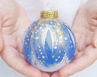 Un véritable joyau pour votre arbre de Noël! Notre gamme d'ornements inspirés Fabergé regardent comme ils appartiennent dans les plus belles boîtes à bijoux. Tout le monde de ces ornements est peint à la main et aucuns deux jamais le même n'aspect.  Nous avons commencé avec une boule de verre clair et peint à la main un design léger avec de la peinture nacrée fine.  Riche, des accents d'or et perle-blanc ont été peint à la main avec de la peinture de verre fin pour un effet tridimensionnel…