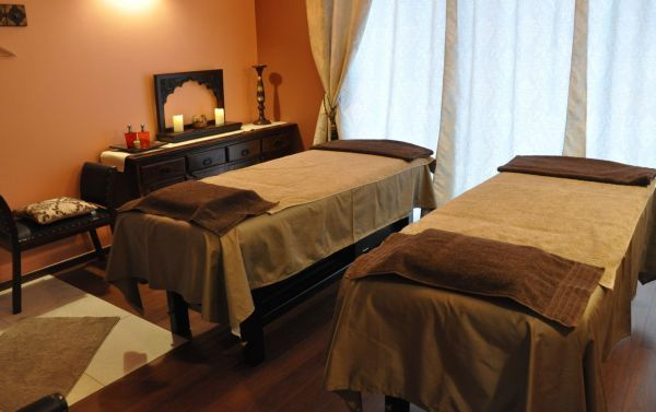 """Salon masażu tajskiego. Pokój dla par. Masaż stóp i nóg (refleksologia) obejmuje m.in. masaż podeszwy, grzbietu stopy, palców, kostek, łydek, okolic kolana. Poprzez działanie na strefy refleksologiczne stóp wspomaga odtruwanie organizmu z toksyn, poprawia sen, usuwa uczucie """"ciężkich nóg"""". Wpływa również na procesy trawienne, system hormonalny, gruczoły limfatyczne i centralny system nerwowy."""
