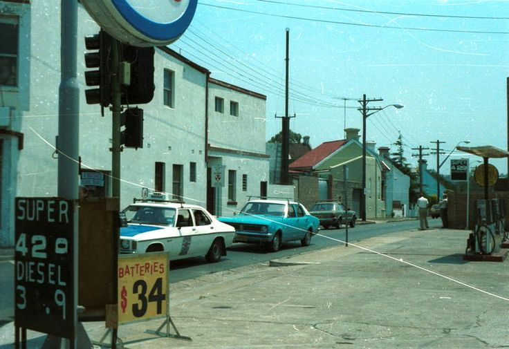 1983. Angel Street, looking north from the corner of King St. The Esso petrol station at 536A King Street with signs for 'A' Abergales Floral Service' and 'Help Make City of Sydney a Nuclear Free Zone' on other side of street / Taxi visible.