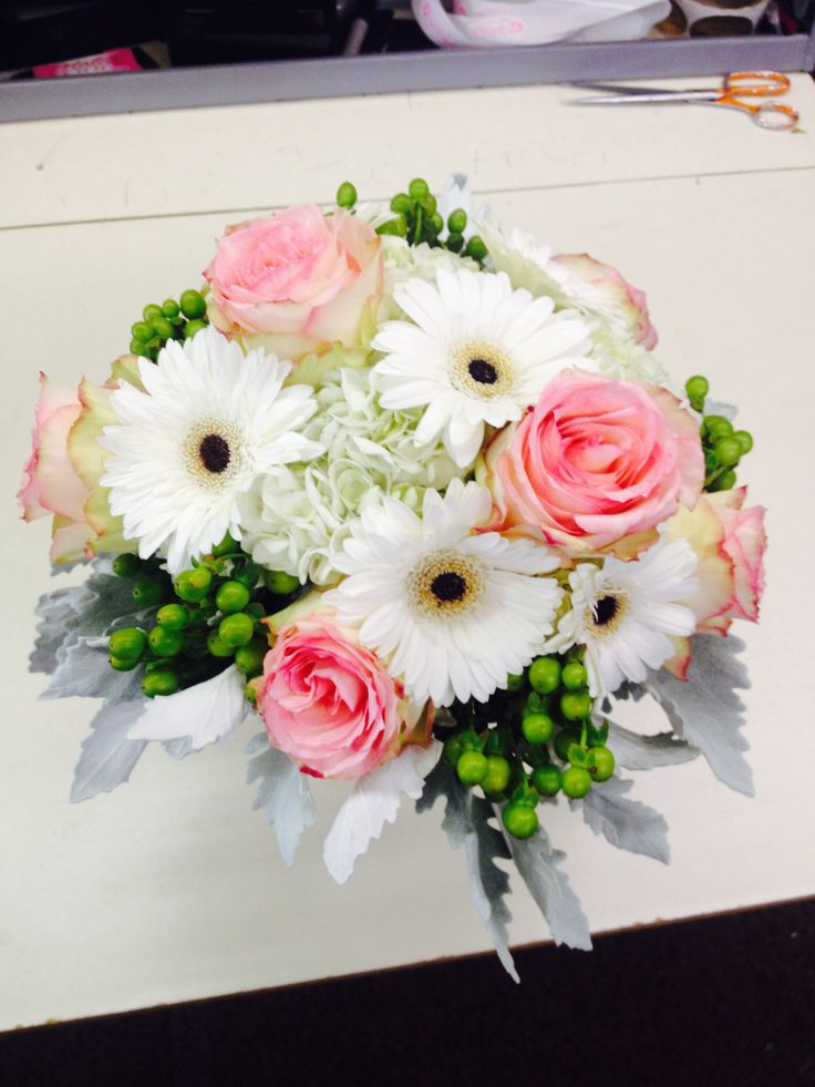 Hydrangea, mini Gerber daisies, open roses and hypericum berries surrounded by dusty miller.