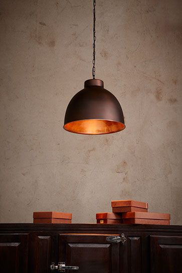 a pendant light that features an antique finish exterior with a copper interior the reflective interior makes the light glow beautifully