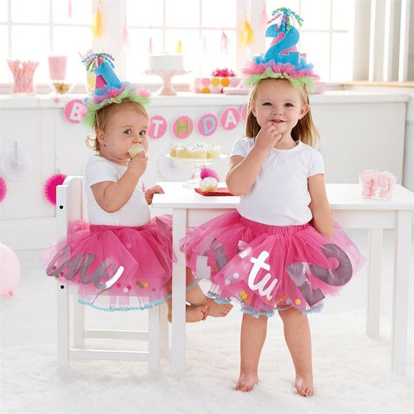 This tiered mylar filled tulle tutu features the number 1 or 2mylar number and word cut-outs to match, with pom-pom decorations and colorful ric-rac trim. Cele