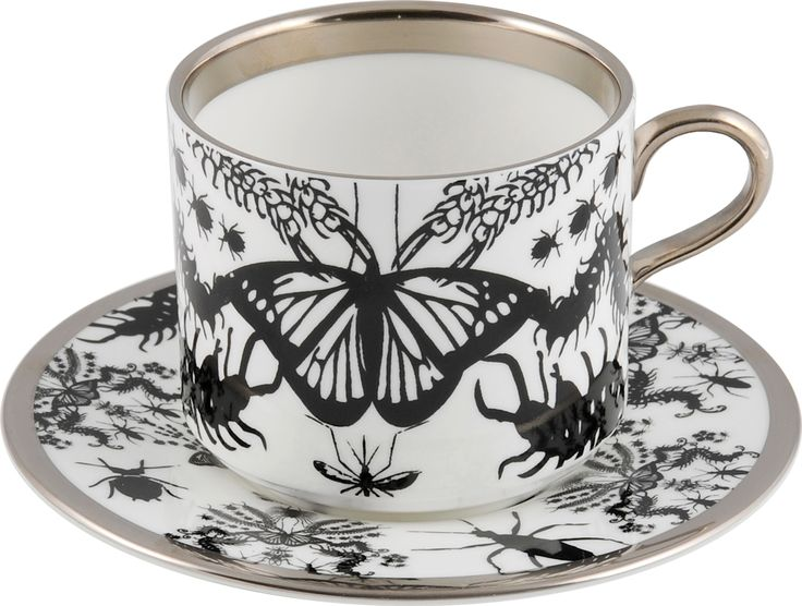 'Entomo' Black Latte Cup & Saucer – A beautiful piece, perfect to enjoy your favourite hot drink. Entomo presents an array of some of the most important yet often misunderstood creatures on our planet. From gossamer wings of the butterfly to the architectural magnificence of the stag beetle, together a pattern of wonderment and delight. Designed by Monica Tsang. Handwash Only. Hand gilded platinum rim and handle. Available in Black and Platinum. Made in Stoke-on-Trent, England. Fine Bone…