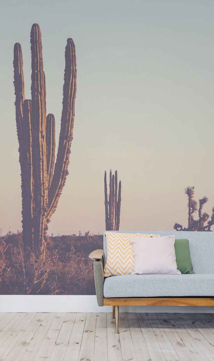 Create a dreamy desert feel to your interiors with this landscape wallpaper. A faint turquoise fades into a coral pink, to give a beautiful pastel coloured sky that sets the scene for a group of cacti. This landscape wall mural is perfect for modern interiors looking for an exotic feel.
