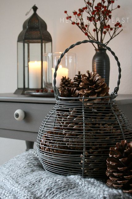 Winter colors: brown and grey. Wire basket filled with pinecones, with grey knit throw
